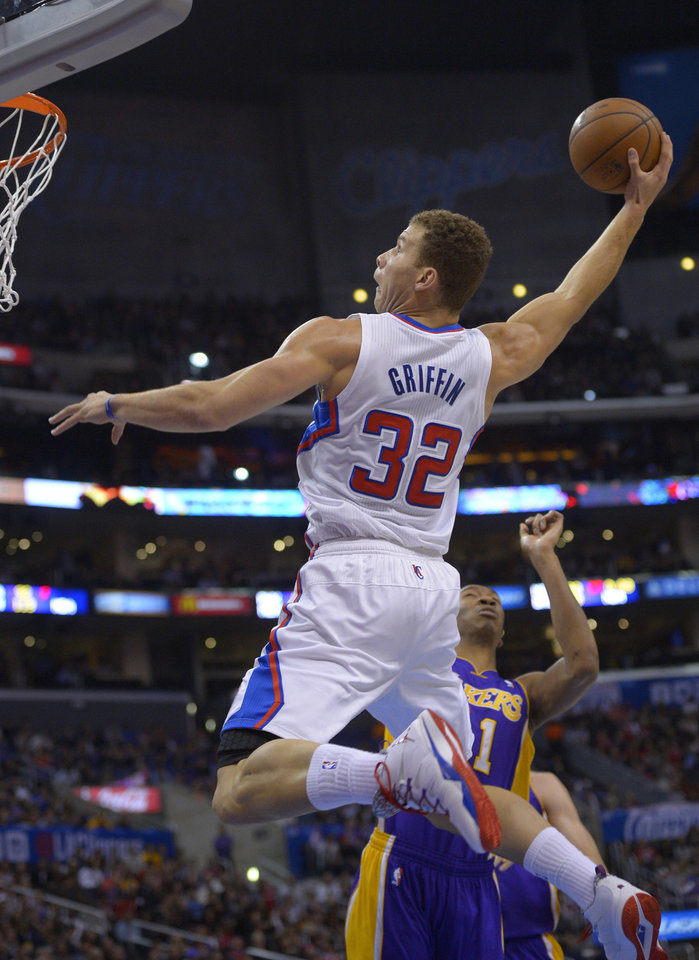Photo - Los Angeles Clippers forward Blake Griffin goes up for a dunk as Los Angeles Lakers guard Wesley Johnson defends during the first half of an NBA basketball game, Friday, Jan. 10, 2014, in Los Angeles. (AP Photo/Mark J. Terrill)