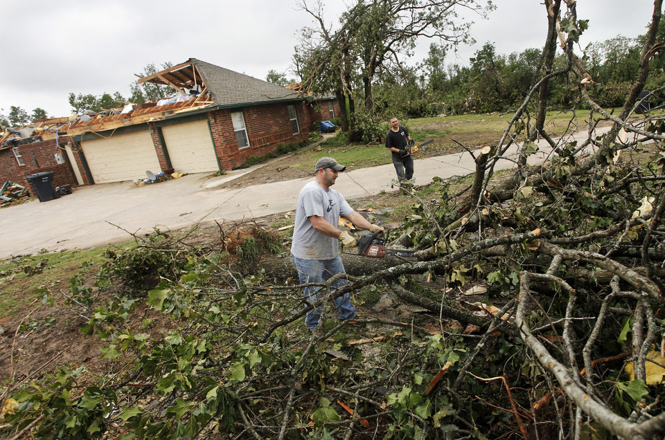 Photo - Dustin Moss, left, and Rory Farmer cut up trees to remove in the Dripping Springs Estates Saturday, May 15, 2010. Saturday hundreds of volunteers went into areas that had been affected by last week's tornadoes to help clear debris. Photo by Doug Hoke, The Oklahoman.