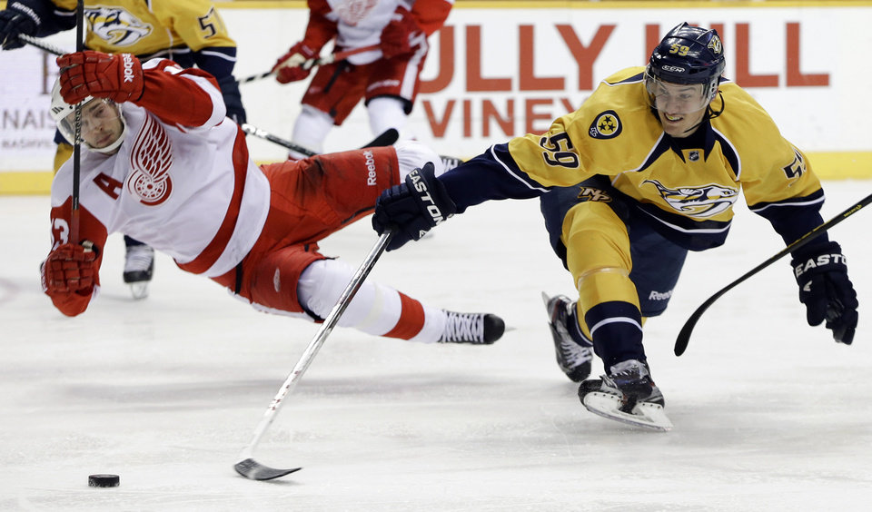 Nashville Predators defenseman Roman Josi (59), of Switzerland, and Detroit Red Wings center Pavel Datsyuk (13), of Russia, collide in the third period of an NHL hockey game on Tuesday, Feb. 19, 2013, in Nashville, Tenn. (AP Photo/Mark Humphrey)
