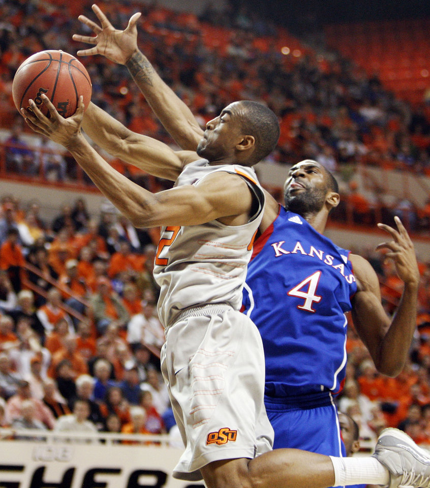 Photo - OSU's Markel Brown (22) moves to the hoop as KU's Justin Wesley (4) defends during a men's college basketball game between the Oklahoma State University Cowboys and the University of Kansas Jayhawks at Gallagher-Iba Arena in Stillwater, Okla., Monday, Feb. 27, 2012. Photo by Nate Billings, The Oklahoman
