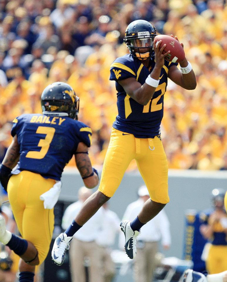 West Virginia quarterback Geno Smith (12) jumps for a high snap before handing off to Stedman Bailey (3) during their NCAA college football game against Baylor in Morgantown, W.Va., Saturday, Sept. 29, 2012. (AP Photo/Christopher Jackson)