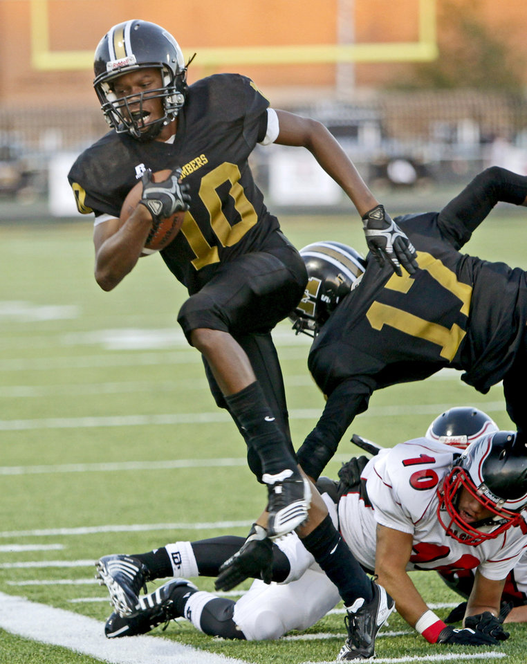 Photo - Midwest City's Cortrael Colbert steps past Del City's Bryce Freeman during a high school football game in Midwest City, Okla., Friday, September 3, 2010.  Photo by Bryan Terry, The Oklahoman