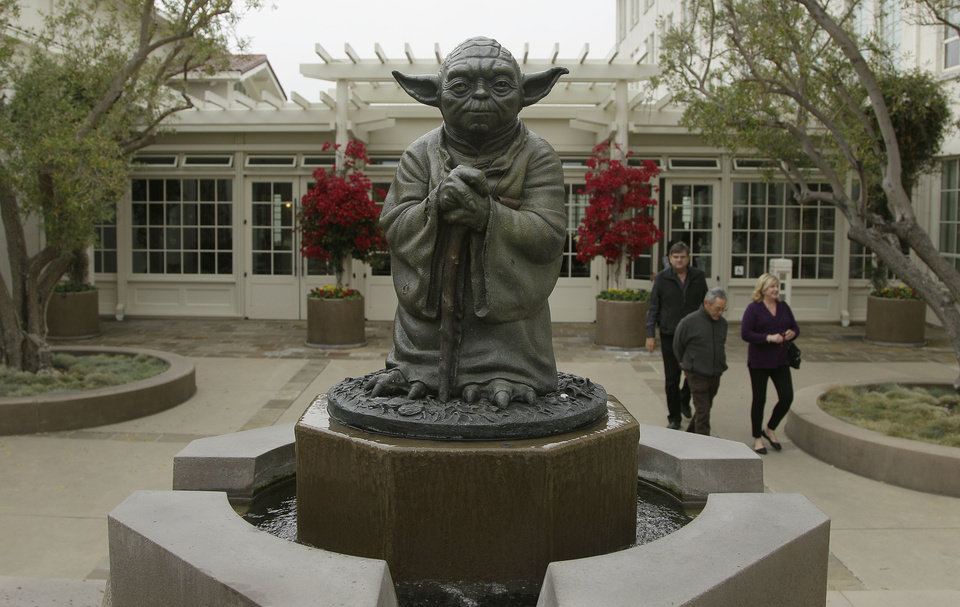 Photo -   People walk past a fountain showing the Yoda character from the Star Wars movies outside of Lucasfilms headquarters in San Francisco, Tuesday, Oct. 30, 2012. The Walt Disney Co. announced Tuesday that it was buying Lucasfilm Ltd. for $4.05 billion. (AP Photo/Jeff Chiu)