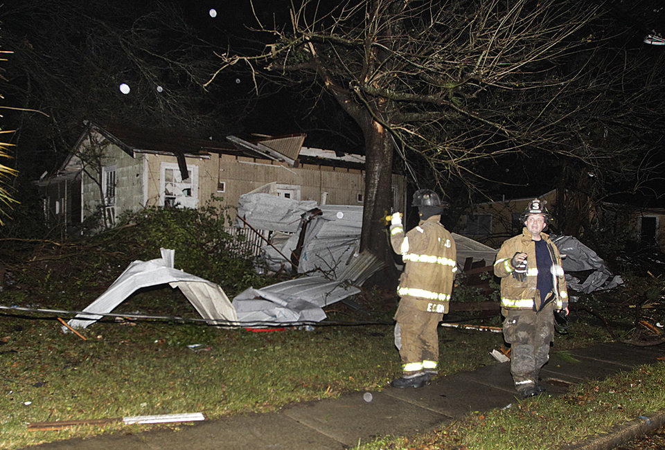 Photo - Firefighters go door-to-door on North Carlen Street in the Midtown section of Mobile, Ala. after a tornado touched down Tuesday, Dec. 25, 2012. A Christmas Day twister outbreak left damage across the Deep South while holiday travelers in the nation's much colder midsection battled sometimes treacherous driving conditions from freezing rain and blizzard conditions. (AP Photo/AL.com, Mike Kittrell)  MAGS OUT