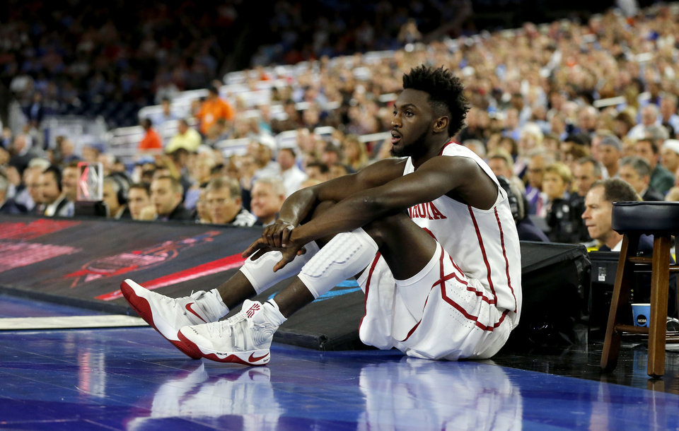 Photo - Oklahoma's Khadeem Lattin (12) sits beside the court during the national semifinal between the Oklahoma Sooners (OU) and the Villanova Wildcats in the Final Four of the NCAA Men's Basketball Championship at NRG Stadium in Houston, Saturday, April 2, 2016. Photo by Nate Billings, The Oklahoman
