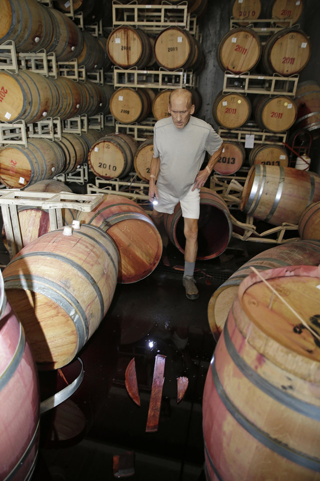 Photo - Winemaker Tom Montgomery walks in wine and looks over damage following an earthquake at the B.R. Cohn Winery barrel storage facility Sunday, Aug. 24, 2014, in Napa, Calif.  Winemakers in California's storied Napa Valley woke up to thousands of broken bottles, barrels and gallons of ruined wine as a result of Sunday's earthquake.  (AP Photo/Eric Risberg)
