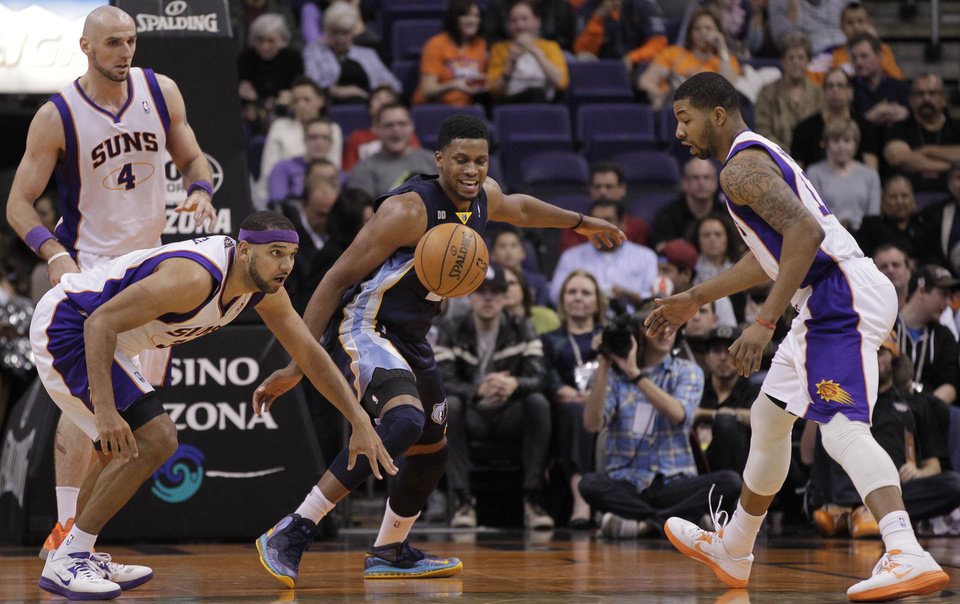 Memphis Grizzlies' Rudy Gay, center, loses the ball as Phoenix Suns' Jared Dudley, left, and Markieff Morris pursue during the second half of an NBA basketball game on Wednesday, Dec. 12, 2012, in Phoenix. (AP Photo/Matt York)