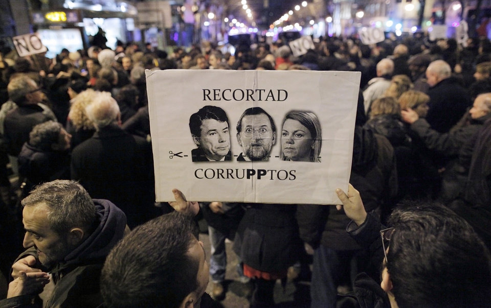 Photo - People hold a banner with pictures of Spanish Prime Minister Mariano Rajoy, and Popular Party's members, María Dolores de Cospedal, and Luis Bracenas, ex treasurer,  reading 'let's cut on corrupts'  as they protest against corruption outside the Popular Party's headquarters in central Madrid, Friday, Jan. 18, 2013. A former Spanish ruling party treasurer amassed 22 million euro ($29 million) in Swiss bank accounts, a court said, prompting a barrage of questions Friday about whether senior officials may have been involved in alleged corruption before taking power in 2011. (AP Photo/Andres Kudacki)