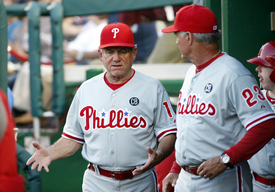 Photo - Philadelphia Phillies bench coach Larry Bowa, left, talks in the dugout with manager Ryne Sandberg during the third inning of a baseball game against the Washington Nationals at Nationals Park Tuesday, June 3, 2014, in Washington. (AP Photo/Alex Brandon)