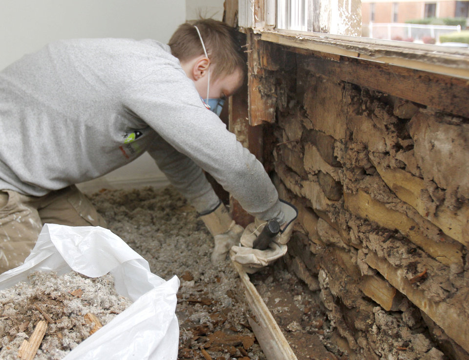 Emily Leftwich works to reconstruct a section of an exterior wall on Thursday on a home at 2229 NE 21.  By Paul Hellstern, The Oklahoman <strong>PAUL HELLSTERN - Oklahoman</strong>