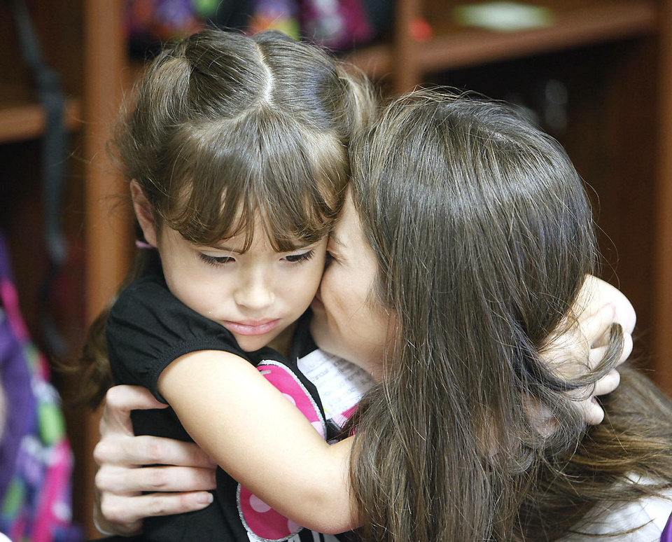 Photo - Marissa Algarin, 5, gets a hug and kiss from her mom, Margaret,  at Frontier Elementary School as Edmond Schools begins classes for the new school year in Edmond, OK, Tuesday, August 20, 2013,  Photo by Paul Hellstern, The Oklahoman