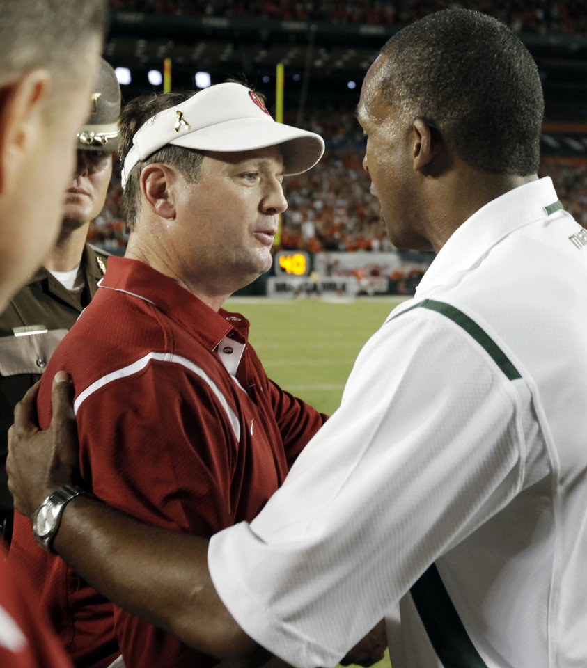 Photo - OU head coach Bob Stoops, left, talks with Miami head coach Randy Shannon after the college football game between the University of Oklahoma (OU) Sooners and the University of Miami (UM) Hurricanes at Land Shark Stadium in Miami Gardens, Florida, Saturday, October 3, 2009. Miami won, 21-20. Photo by Nate Billings, The Oklahoman