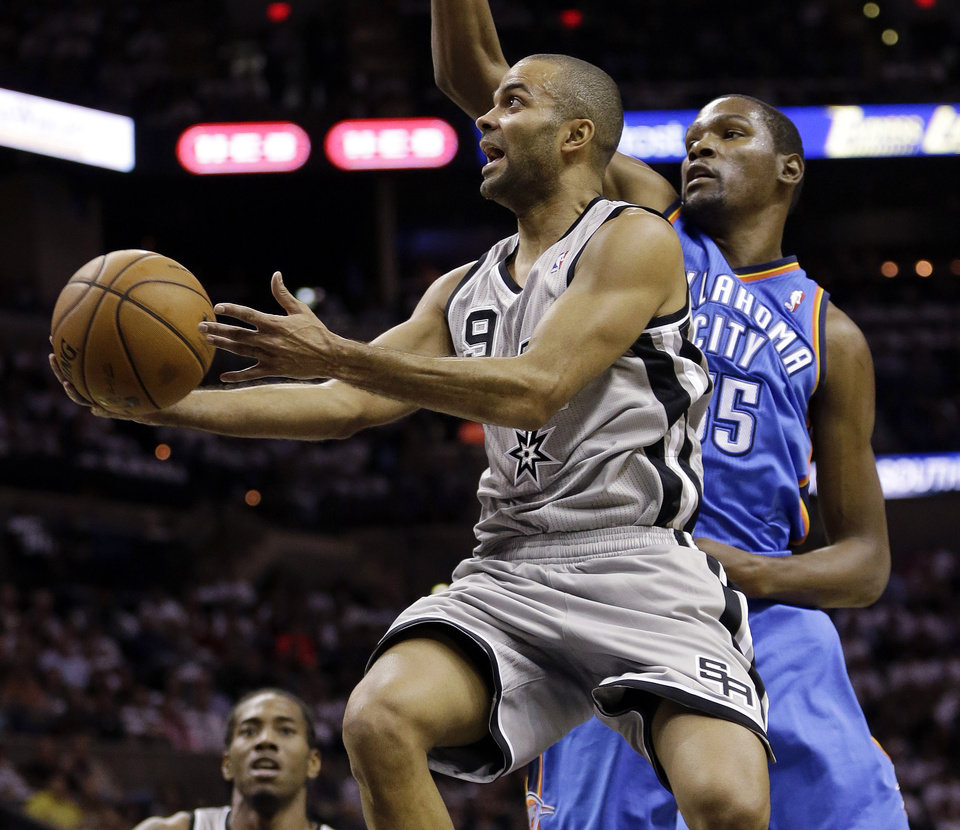 San Antonio Spurs\' Tony PArker, left, of France, drives to the basket as Oklahoma Thunder\'s Kevin Durant, right, defends during the first quarter of an NBA basketball game, Thursday, Nov. 1, 2012, in San Antonio. (AP Photo/Eric Gay) ORG XMIT: TXEG101
