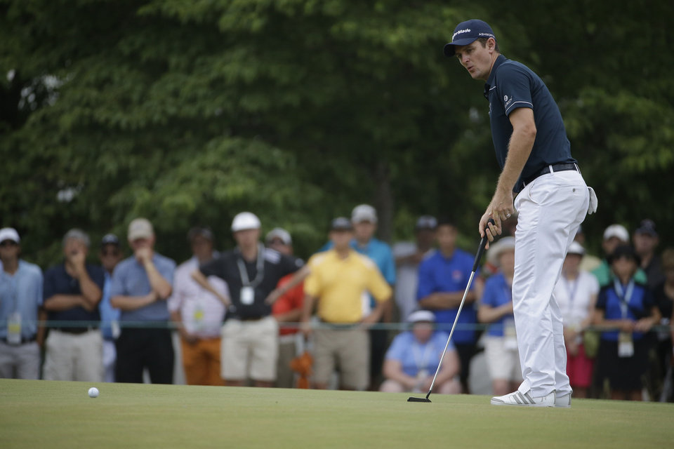 Photo - Justin Rose, of England, watches his putts on the 12th hole during the first round of the U.S. Open golf tournament in Pinehurst, N.C., Thursday, June 12, 2014. (AP Photo/David Goldman)
