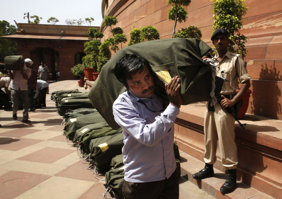 Photo - An Indian worker carries a sack containing copies of the 2014-15 union budget at the Indian parliament in New Delhi, Thursday, July 10, 2014. India's new government has introduced an ambitious reform-minded budget focusing on promoting manufacturing and infrastructure, raising the tax base and overhauling populist subsidies. (AP Photo/Manish Swarup)