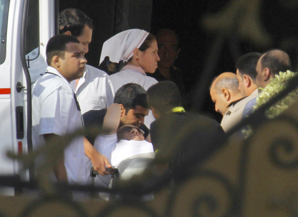 Photo - Medics escort former Egyptian President Hosni Mubarak, 85, into an ambulance after after he was flown by a helicopter ambulance to the Maadi Military Hospital from Tora prison in, Cairo, Thursday, Aug. 22, 2013. Mubarak has been released from jail and taken to military hospital in Cairo. (AP Photo/Amr Nabil)