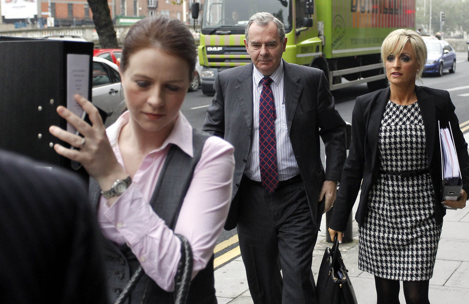 FILE This , Friday, Oct. 19, 2012 file photo shows Sean Quinn, center, arriving at the High court with his daughter-in-law Karen Woods, right, in Dublin, Ireland. A judge in Ireland on Friday Nov. 2, 2012 ordered bankrupt tycoon Sean Quinn jailed for nine weeks for failing to observe orders to stop placing foreign property assets beyond the reach of creditors. Quinn � Ireland's richest man until 2008 � faces financial ruin because of his reckless gamble that year on Anglo Irish Bank. The Dublin lender was the biggest financier of Ireland's runaway property market, a boom that imploded in 2009. (AP Photo/Peter Morrison)