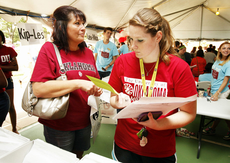Photo - Taylor Garrett, right, from Dewey, checks in at the University of Oklahoma as she and her mother, Whitney Garrett, left, arrive on campus Thursday.