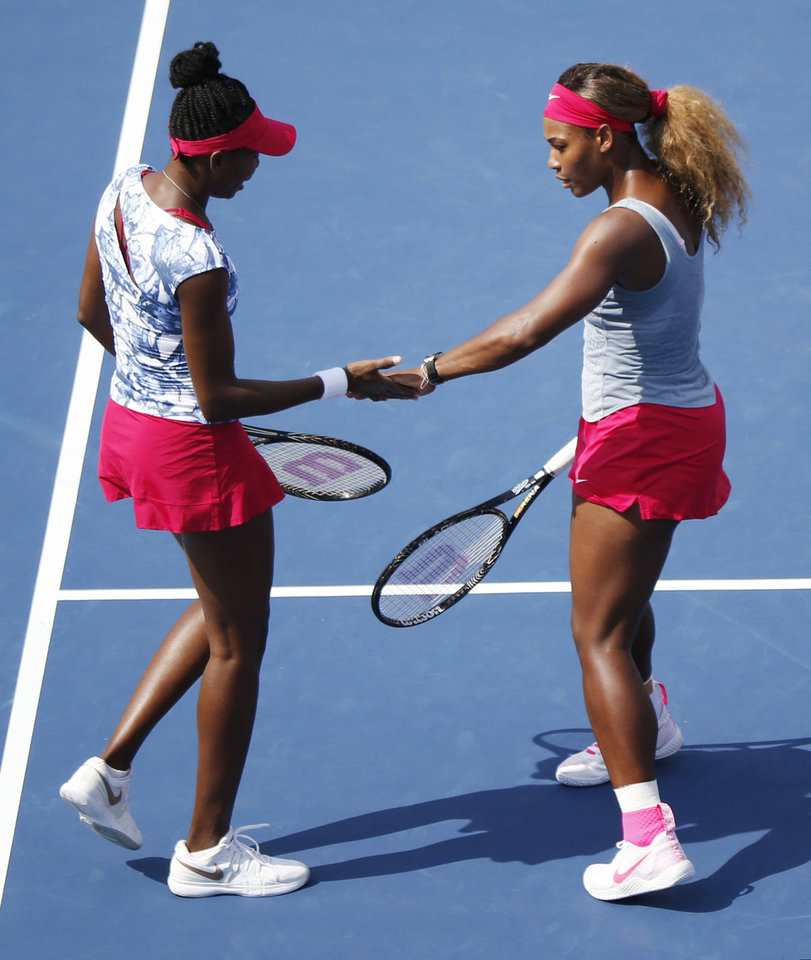 Photo - Venus Williams and Serena Williams slap hands between points against Garbine Muguruza and Carla Suarez Navarro, of Spain, during a doubles match at the 2014 U.S. Open tennis tournament, Sunday, Aug. 31, 2014, in New York. (AP Photo/Seth Wenig)
