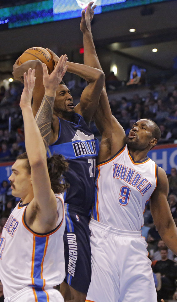 Photo - Oklahoma City's Serge Ibaka (9) and Steven Adams (12) defend on Dallas' Jeremy Evans (21) during the NBA basketball game between the Oklahoma City Thunder and the Dallas Mavericks at Chesapeake Energy Arena on Wednesday, Jan. 13, 2016, in Oklahoma City, Okla.  Photo by Chris Landsberger, The Oklahoman