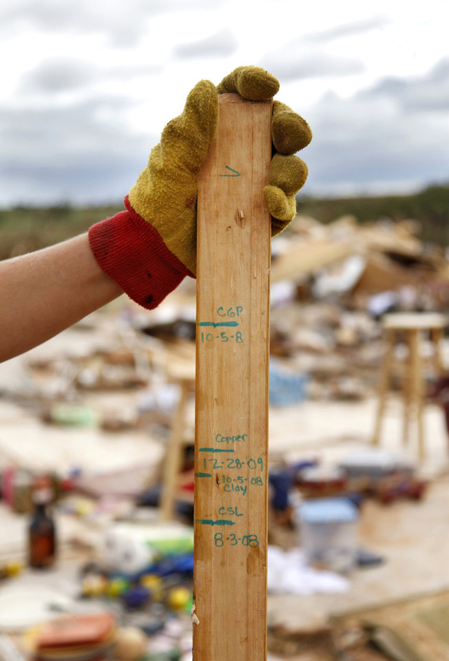 Miranda Lewis holds the recovered growth marker used by her six-year-old son Copper from the rubble where their house once stood west of El Reno, Wednesday, May 25, 2011. Photo by Chris Landsberger, The Oklahoman