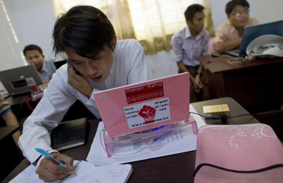 "In this March 14, 2013 photo, Min Htet San, political editor of weekly journal ""The Voice,"" speaks on his mobile phone as a campaign motto displays in his laptop cover in Yangon, Myanmar. The Voice Weekly news journal was temporarily suspended for 6-times during the period of 2005-2012. After eight months and 26 hearings, Myanmar�s ministry of mining dropped its controversial defamation lawsuit against the journal in early 2013. The lawsuit originated from publication of corruption allegations against the ministry in 2012. Myanmar's newly energized press corps is calling on the government to revise a proposed new publishing law, saying it will mark a severe setback to press freedoms and replace the country's old censorship regime with other forms of repression. (AP Photo/Gemunu Amarasinghe)"