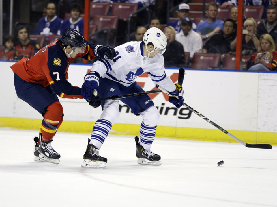 Photo - Florida Panthers defenseman Dmitry Kulikov (7) and Toronto Maple Leafs left wing James van Riemsdyk (21) chase the puck in the first period of an NHL hockey game on Thursday, April 10, 2014, in Sunrise, Fla. (AP Photo/Lynne Sladky)