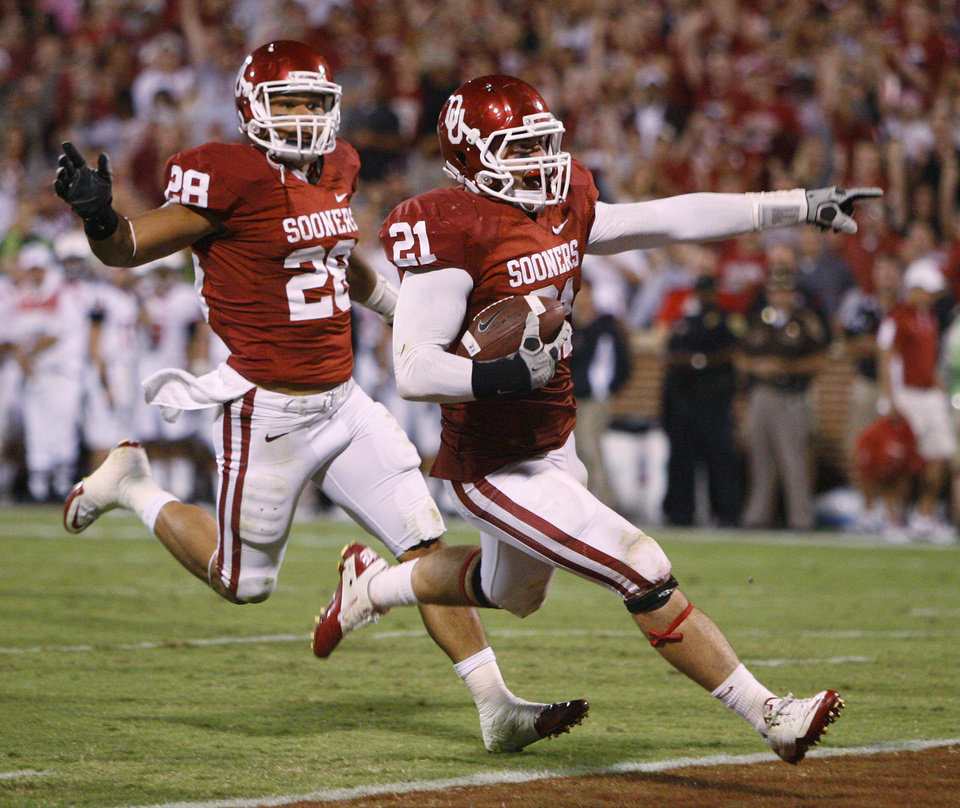 Photo - Oklahoma's Tom Wort (21) scores a touchdown after Oklahoma's Travis Lewis (28) forced a fumble during the college football game between the University of Oklahoma Sooners (OU) and the Ball State Cardinals at Gaylord Family-Memorial Stadium on Saturday, Oct. 01, 2011, in Norman, Okla. Oklahoma won 62-6. Photo by Bryan Terry, The Oklahoman