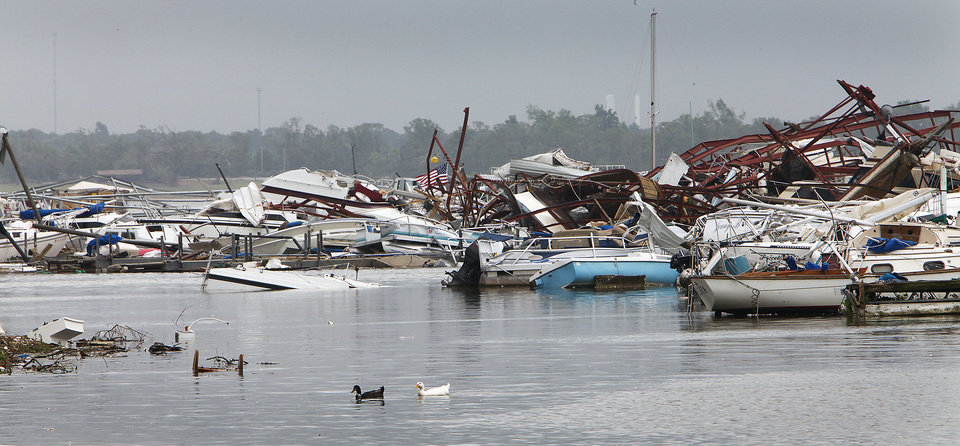 Photo - Ducks swim by the boats damaged by the tornado at the marina at Lake Thunderbird State Park on Alameda in Norman, Tuesday, May 11, 2010.    Photo by David McDaniel, The Oklahoman