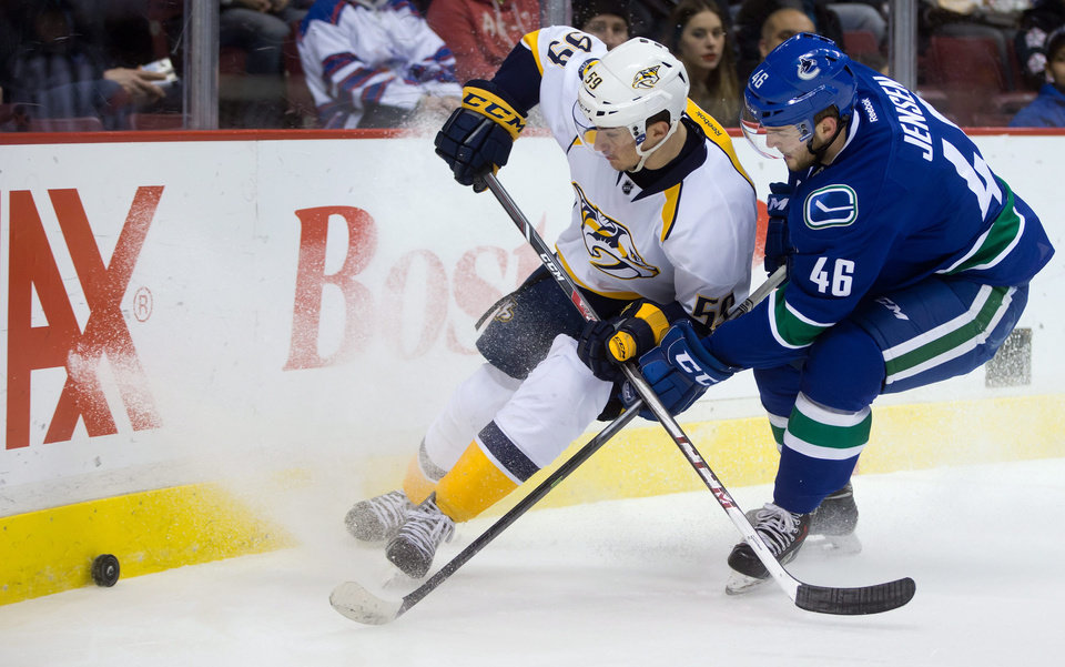 Photo - Vancouver Canucks' Nicklas Jensen, right, of Denmark, checks Nashville Predators' Roman Josi, of Switzerland, during first-period NHL hockey game action in Vancouver, British Columbia, Wednesday, March 19, 2014. (AP Photo/The Canadian Press, Darryl Dyck)