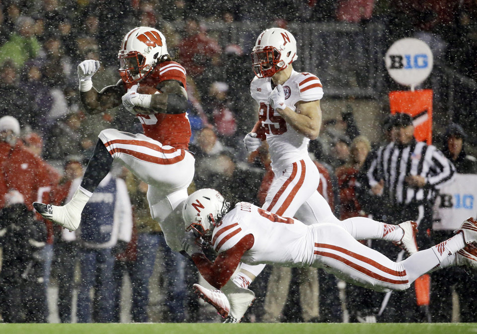 Photo - Wisconsin's Melvin Gordon breaks away from Nebraska's Corey Cooper for  a 26-yard touchdown in the third quarter of an NCAA college football game, Saturday, Nov. 15, 2014, in Madison, Wis. Gordon ran for 408 yards through three quarters Saturday, capping it off with this run to break the single-game major college football rushing record set on Nov. 20, 1999, when LaDanian Tomlinson with 406 yards on 43 carries for TCU against UTEP. (AP Photo/Morry Gash)