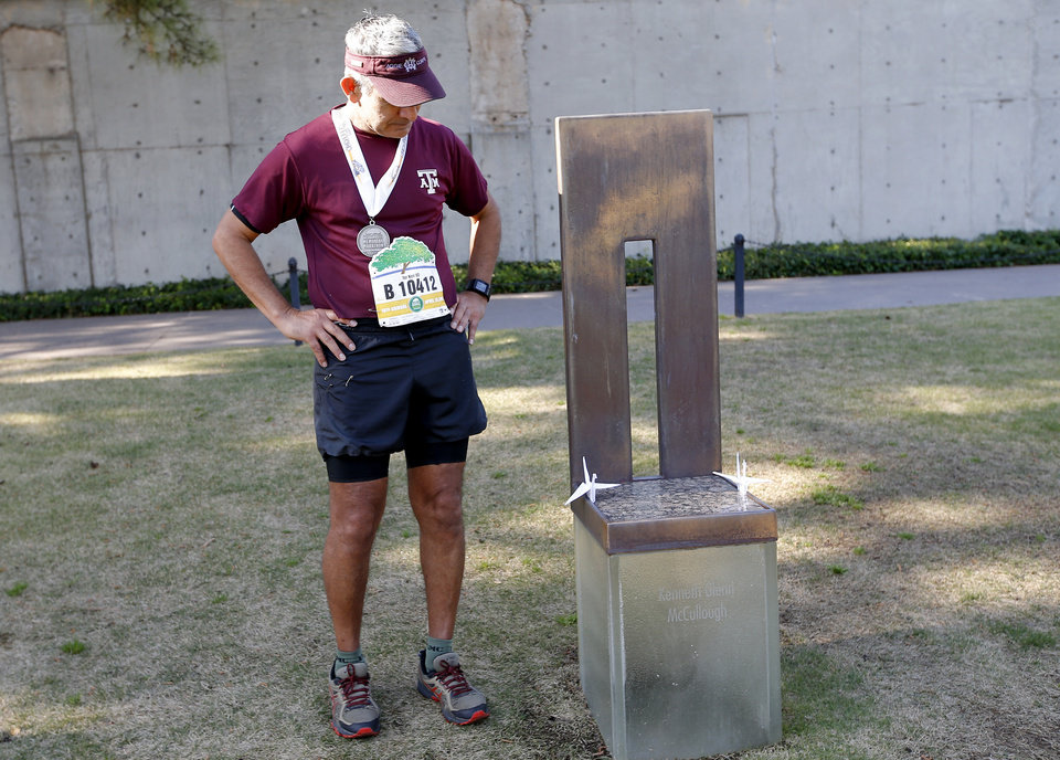 Photo - Acension Fierro takes a moment at the memorial chair of his college friend Kenneth McCullough following the Oklahoma City Marathon in Oklahoma City,  Sunday, April 29, 2018. Kenneth McCullough participated in the Sabre arch at his wedding. Photo by Sarah Phipps, The Oklahoman