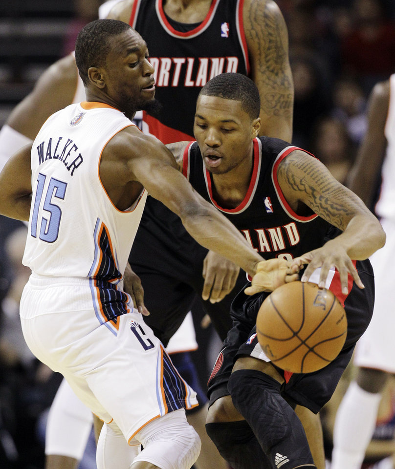 Photo - Charlotte Bobcats' Kemba Walker (15) steals the ball from Portland Trail Blazers' Damian Lillard, right, during the first half of an NBA basketball game in Charlotte, N.C., Monday, Dec. 3, 2012. (AP Photo/Chuck Burton)