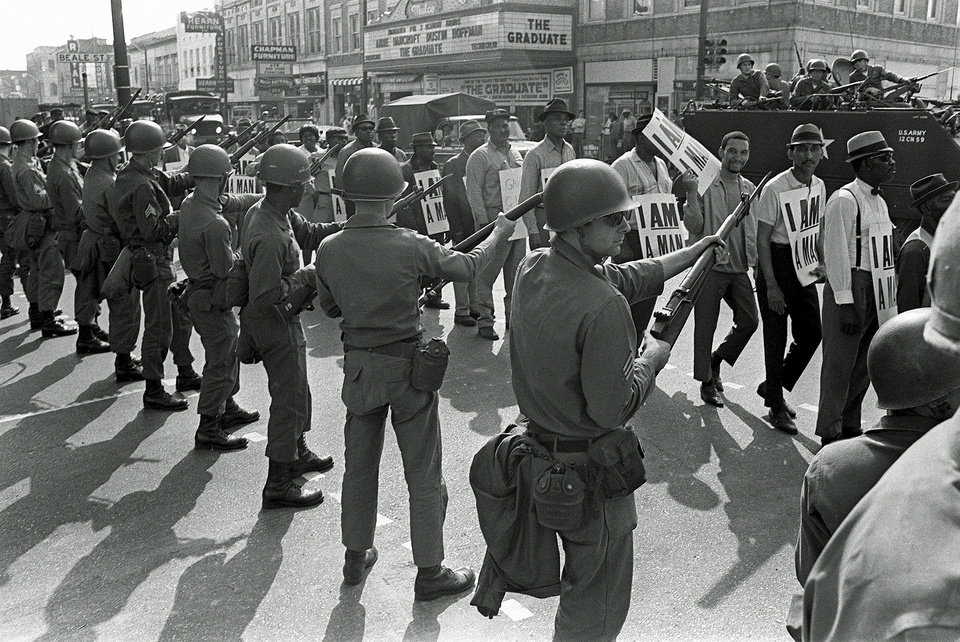 Photo - FILE -In this March 29, 1968 file photo, Striking sanitation workers and their supporters are flanked by bayonet-wielding National Guard troops and armored vehicles during a march on City Hall in Memphis, Tenn., one day after a similar march erupted in violence, leaving one person dead and several injured. Forty-five years after Martin Luther King Jr. was killed supporting a historic sanitation workers strike in Memphis, the city's garbage and trash collectors are fighting to hold on to jobs that some city leaders want to hand over to a private company. (AP Photo/Charlie Kelly, File)