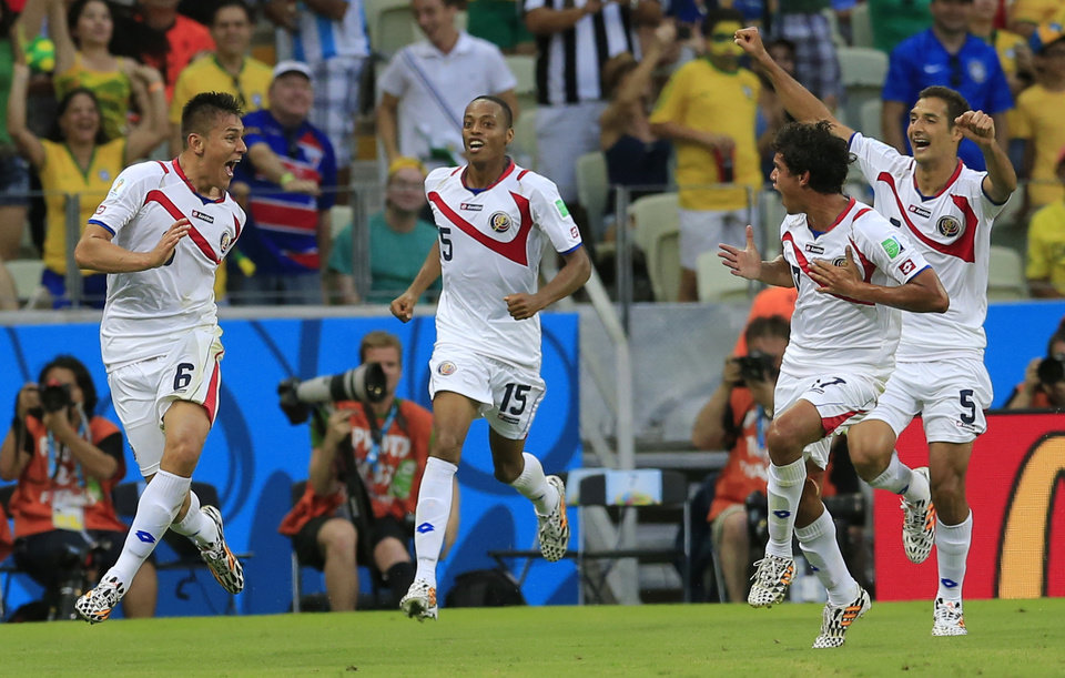 Photo - Costa Rica's Oscar Duarte, left, celebrates after scoring his side's second goal during the group D World Cup soccer match between Uruguay and Costa Rica at the Arena Castelao in Fortaleza, Brazil, Saturday, June 14, 2014. (AP Photo/Bernat Armangue)