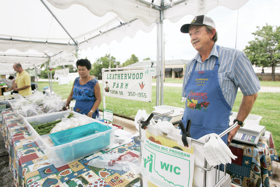 Photo - Bud and Lita Leatherwood of Yukon post a sign that their stand at the OSU-OKC Chesapeake Farmers Market, NW 63 and Western, is approved for the Women, Infants and Children program.  PHOTO BY Steve Gooch, The Oklahoman