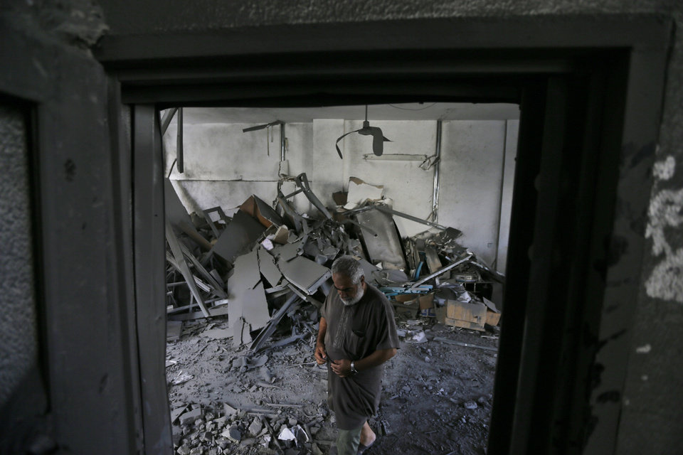 Photo - Palestinian psychiatrist Mahmoud Shiam, 60, inspects his destroyed home from an overnight Israeli strike, in Gaza City, Monday, July 21, 2014. On Sunday, the first major ground battle in two weeks of Israel-Hamas fighting exacted a steep price, killing scores Palestinians and over a dozen Israeli soldiers and forcing thousands of terrified Palestinian civilians to flee their devastated Shijaiyah neighborhood, which Israel says is a major source for rocket fire against its civilians. (AP Photo/Lefteris Pitarakis)