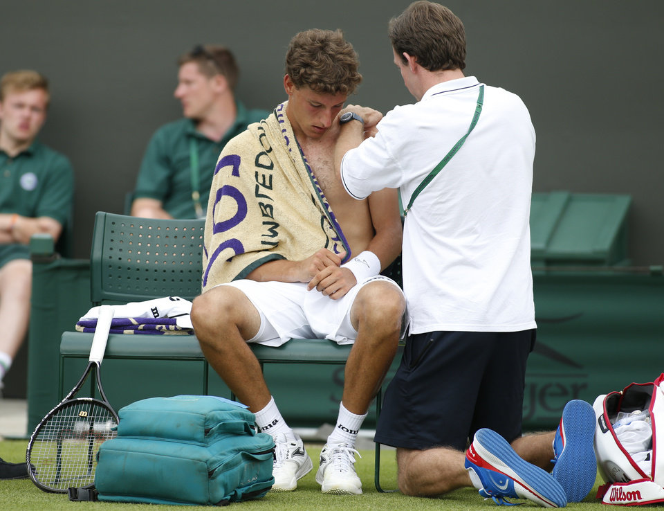 Photo - Pablo Carreno Busta of Spain is being checked by a member of the medical team during his first round match against David Ferrer of Spain at the All England Lawn Tennis Championships in Wimbledon, London,  Monday, June  23, 2014. (AP Photo/Alastair Grant)