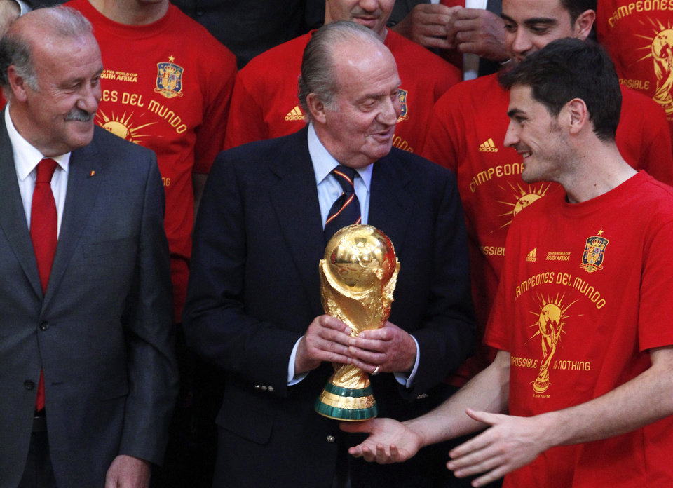 Photo - FILE - In this Tuesday, July 12, 2010, file photo, Spain's King Juan Carlos, center, holds the World Cup soccer trophy next to winning goalkeeper Iker Casillas, right, and coach Vicente del Bosque, left, at the Royal Palace in Madrid. Spain's King Juan Carlos plans to abdicate and pave the way for his son, Crown Prince Felipe, to take over, Spanish Prime Minister Mariano Rajoy told the country Monday in an announcement broadcast nationwide. The 76-year-old Juan Carlos oversaw his country's transition from dictatorship to democracy but has had repeated health problems in recent years. (AP Photo/Paul White, File)
