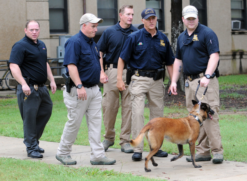 Photo -   Officers with a dog talk after searching Evangeline Hall in Baton Rouge, La., where a bomb threat was received Monday, Sept. 17, 2012. Thousands of students, professors and workers were evacuated from Louisiana State University's main campus following the threat, school officials said. (AP Photo/The Daily Reveille, Catherine Threlkeld)