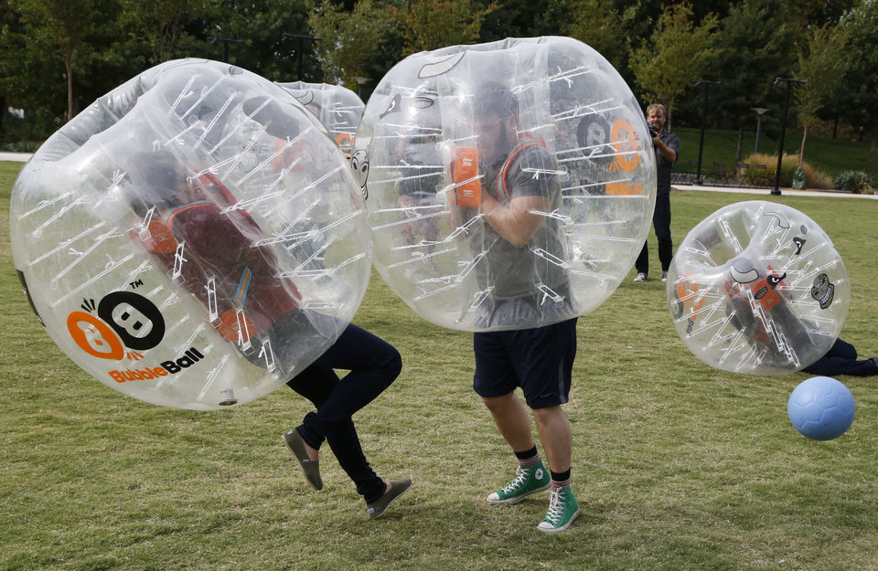 Photo -  Oklahoman writer Adam Kemp bowls over meteorologist Lacey Swope during a bubble soccer match at the Myriad Gardens in Oklahoma City on Friday. [Photo by Paul Hellstern, The Oklahoman]