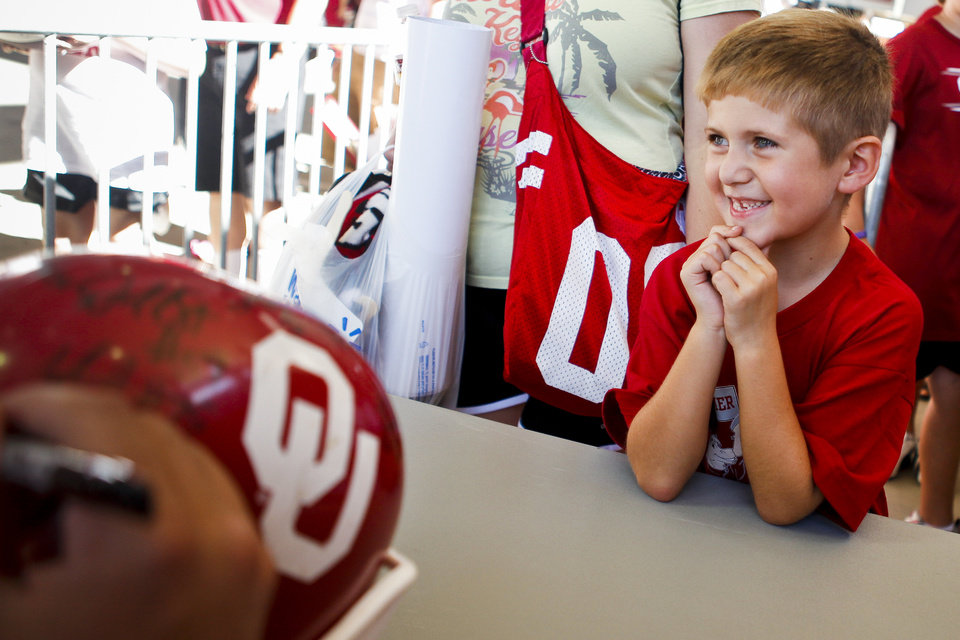 Photo - 6-year-old Michael Boeckman of Moore smiles as he has an OU helmet signed by members of the football team at the University of Oklahoma's Meet the Sooners Day at Gaylord Family