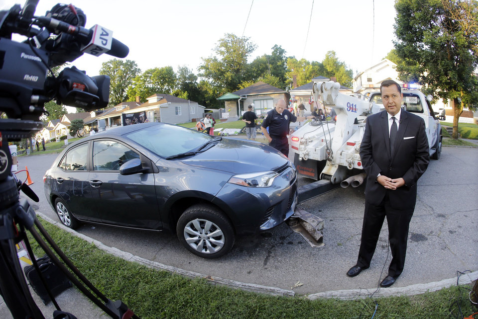 Photo - Television reporter Mario Diaz of New York does a report as a car is towed away to clear the street in front of the boyhood home of Muhammad Ali Friday, June 10, 2016, in Louisville, Ky. Ali's funeral procession is scheduled to pass by the house later in the day. (AP Photo/Mark Humphrey)