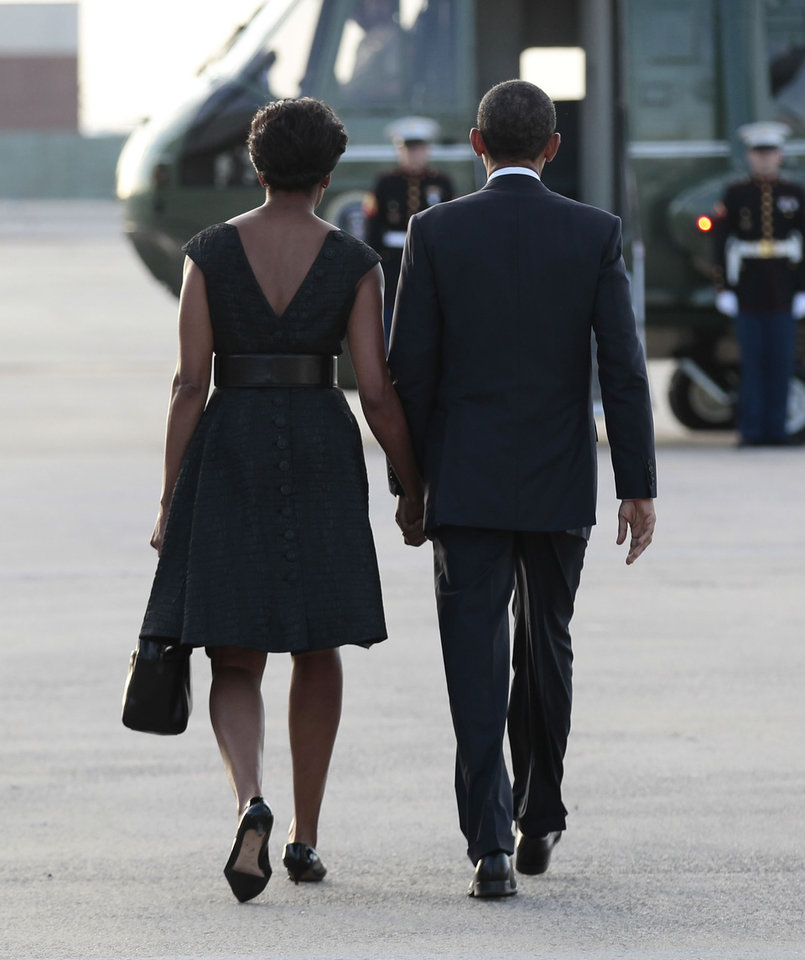 President Barack Obama and first lady Michelle Obama hold hands as they walk toward Marine One helicopter during their arrival at JFK International airport Sunday, Sept., 11, 2011 in New York. (AP Photo/Pablo Martinez Monsivais)