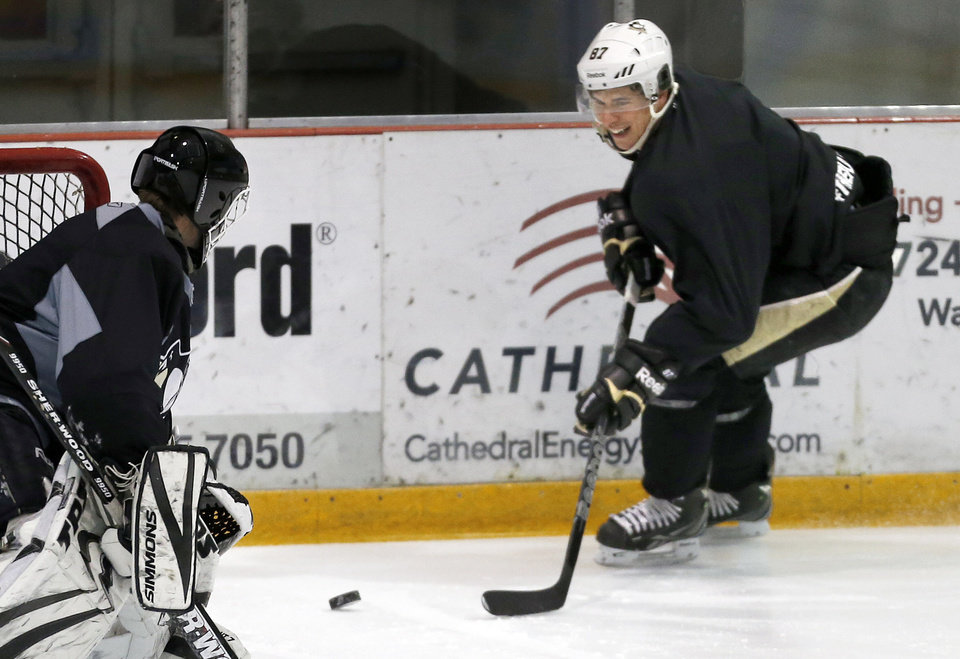 Photo - Pittsburgh Penguins' Sidney Crosby, right, skates in on a goalie during a hockey workout on Thursday, Jan. 3, 2013, at the IceoPlex in Canonsburg, Pa. Crosby knows the NHL season, if and when it starts, will be a sprint. That should favor teams like the Penguins, who endured little turnover in the long offseason. (AP Photo/Keith Srakocic)