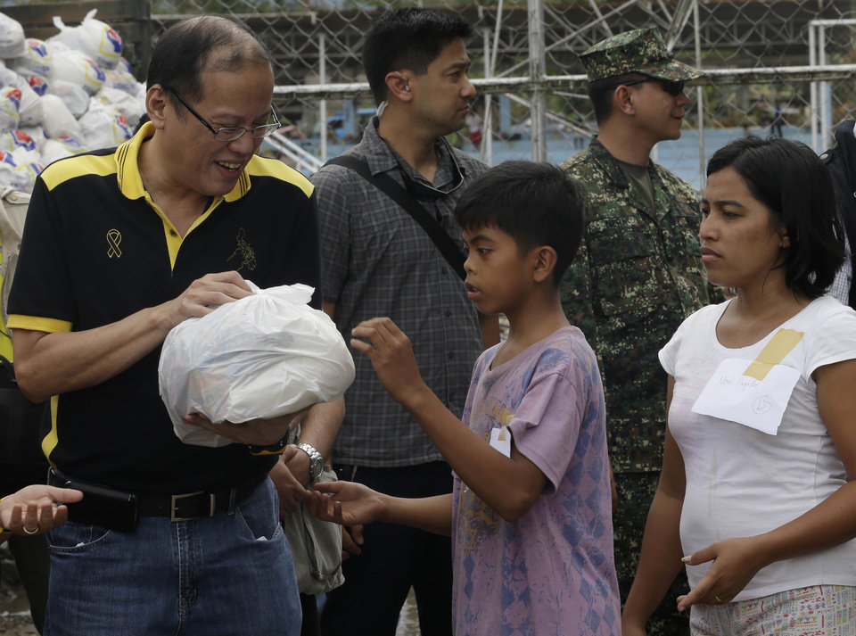Philippine President Benigno Aquino III, left, helps to distribute relief goods to victims of Typhoon Bopha during his visit to New Bataan township, Compostela Valley in southern Philippines Friday Dec. 7, 2012. Rescuers were digging through mud and debris Friday to retrieve more bodies strewn across the farming valley by the powerful typhoon. (AP Photo/Bullit Marquez)