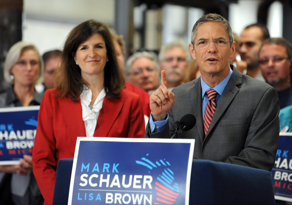 Photo - Democratic gubernatorial candidate Mark Schauer unveils his 10-point jobs plan at a news conference held at the Plumbers and Pipefitters Local 333 training facility in Lansing, Mich. on Tuesday, July 29, 2014. At left is Schauer's running mate, Lisa Brown. (AP Photo/Lansing State Journal, Greg DeRuiter)