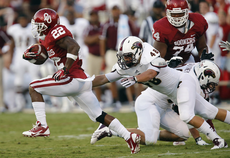 Photo - Oklahoma's Roy Finch (22) runs pst Louisiana Monroe's Hunter Kissinger (48) during the college football game between the University of Oklahoma Sooners (OU) and the University of Louisiana Monroe Warhawks (ULM) at the Gaylord Family Memorial Stadium on Saturday, Aug. 31, 2013 in Norman, Okla.  Photo by Chris Landsberger, The Oklahoman