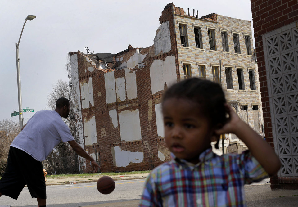 Photo - In this April 8, 2013 picture, a boy whose family asked that he not be identified plays across the street from a partially collapsed row house in Baltimore. The U.S. Census Bureau estimates that 20 percent of American children are impoverished. (AP Photo/Patrick Semansky)