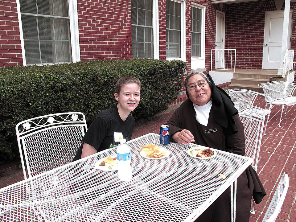 Photo - Faith Lewis, 14, a former Villa Teresa School student, shares a meal with her godmother Sister Sylvia Negrete during the recent Carmelite Sisters of St. Therese's 95th anniversary and alumni gathering at Villa Teresa Convent and School in Oklahoma City. Lewis' mother was a secretary at the popular private Christian school. Photo by Carla Hinton, The Oklahoman